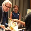 NEW YORK, USA – Dr. Michael Hansen, Senior Scientist of Consumers Union, receives the GOOD WILL Sustainable Development magazine from the representative of the LBV at the event Amanda Vieira.