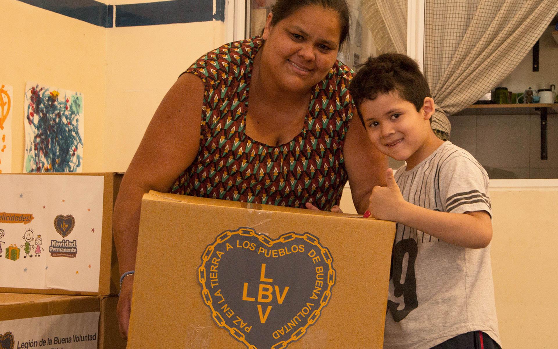 Una mamá del Espacio Educativo Calle Colores (Iguazú 1453 Zavaleta) recibe junto a su hijo la Caja de Navidad.