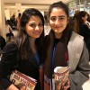 A jovem afegã Duniya Syed (D) está participando do evento e recebeu a revista BOA VONTADE Mulher (em inglês) deNamrata Jadhav, integrante da equipe da LBV no evento.