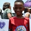 SÁBADO, 8 — Contente, Soldadinho de Deus — como carinhosamente são chamadas as crianças na LBV — mostra as bandeirinhas que levantará durante as palavras fraternas de Paiva Netto.