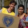 Una mamá de la Escuela Infantil San Francisco de Asís, recibe la Caja de Navidad, junto a su pequeño hijo.
