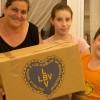 Una mamá del Espacio Educativo Calle Colores (Iguazú 1453 Zavaleta) recibe junto a sus hijos la Caja de Navidad.