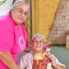 Luque, Paraguay — La Hermana Legionaria Maria Eugenia presenta la revista ¡JESÚS ESTÁ LLEGANDO! a una abuela del Hogar para Ancianos San Francisco de Asís.