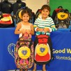 Sisters Cecibel and Gina smiling as they hold their new backpacks at the Oliver St. School distribution.