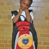 Derrick, a 5-year-old student from the Hawkins St. School so excited to hold his brand new backpack filled with all the materials he'll need for Kindergarten!