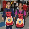 Two kids from the YMCA Shelter of Newark holding back their excitement as they hold their new backpacks.