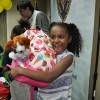 The smiling girl recevies her new backpack at our Backpacks for a Bright Future event held at the YMCA in Newark.