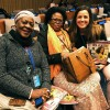 Henriette Tshimuanga Minchiabo, chefe do Departamento do Ministério do Trabalho, Emprego e Previdência Social, da República Democrática do Congo, e Angélique Inzun Okomba, secretária-geral de Emprego e Trabalho, do Ministério do Trabalho, Emprego e Previdência Social, da República Democrática do Congo, recebem os cumprimentos e a revista BOA VONTADE Mulher de Sâmara Malaman, da LBV.